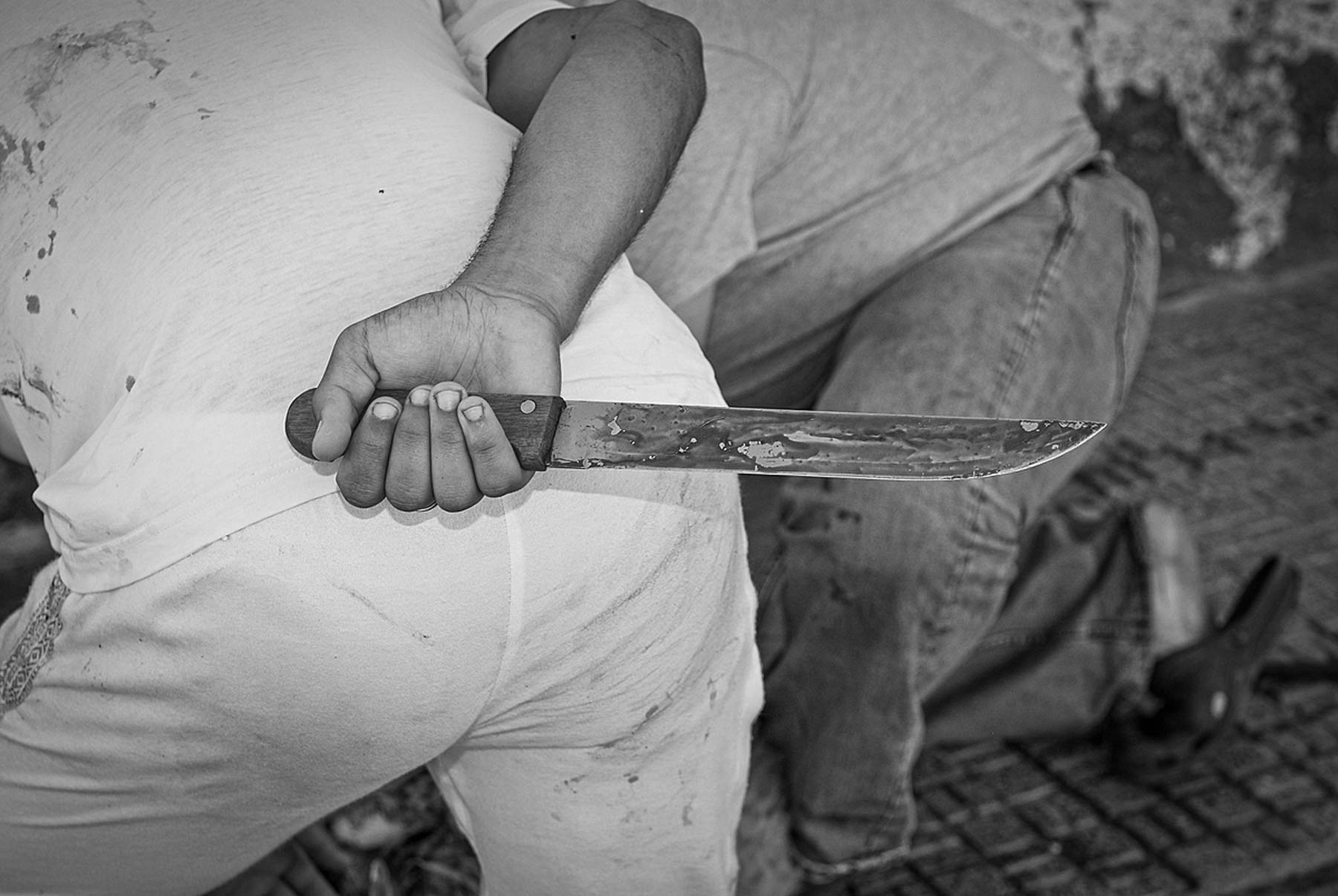 Knife at the ready, a man helps restrain an animal before cutting her throat